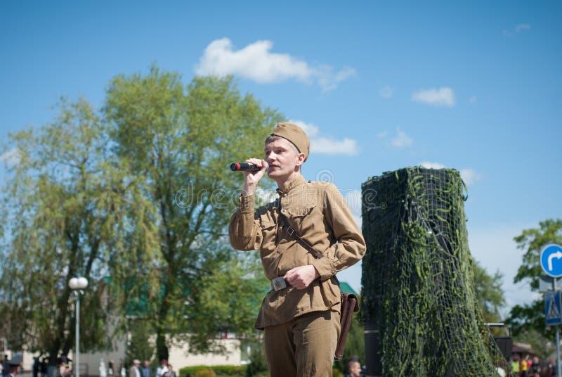 LUBAN, BIELORUSSIA - 9 MAGGIO 2015: un uomo che porta l'uniforme di un soldato sovietico canta una canzone in scena immagini stock