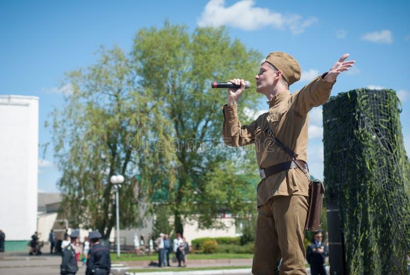 LUBAN VITRYSSLAND - MAJ 9, 2015: en man som bär likformign av en sovjetisk soldat, sjunger en sång på etapp fotografering för bildbyråer