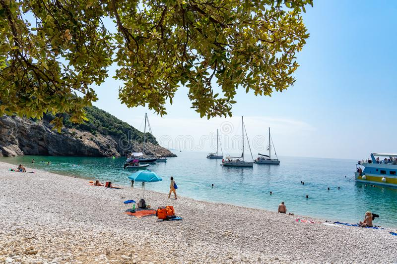 Lubenice beach with tousist and ships in Cres island Croatia with crystal clear turquoise water and atree shade.  stock photos