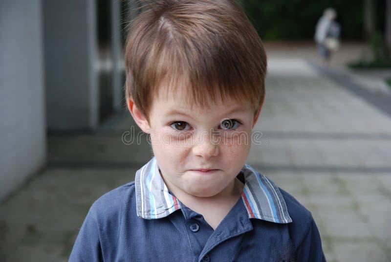 Lubię psota, sowizdrzalska przyglądająca chłopiec obraz royalty free