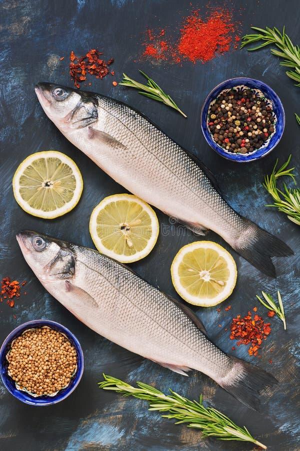 Lubina e ingredientes de los pescados frescos para cocinar - limón, romero, paprika, sumac, coriandro, paprika Pescados crudos en fotografía de archivo