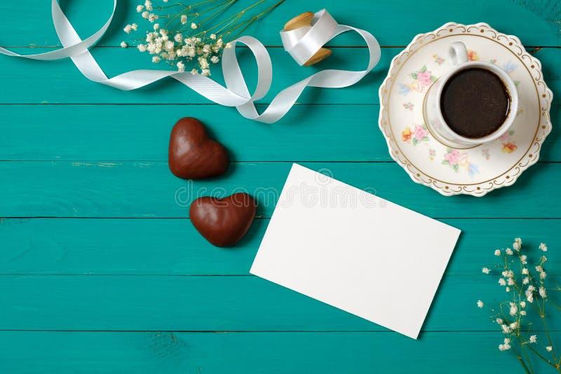 ?lubny ranku poj?cie Zaproszenie karta, sercowata czekolada, fili?anka kawy, stokrotka kwitnie Elegancki minimalny kobiety biurko obraz royalty free