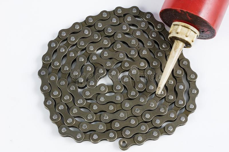 Lubricating the bicycle chain with liquid lubricant. Periodic se. Rvicing of parts for two-wheelers. Light background stock image
