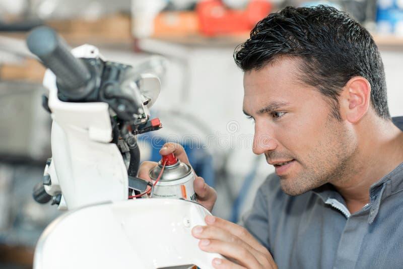 Lubrificante di spruzzatura del meccanico sul motorino fotografia stock