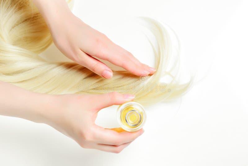 Lubrifichi il trattamento dei capelli per la donna con capelli biondi su fondo bianco Stazione termale, salone di bellezza fotografia stock libera da diritti
