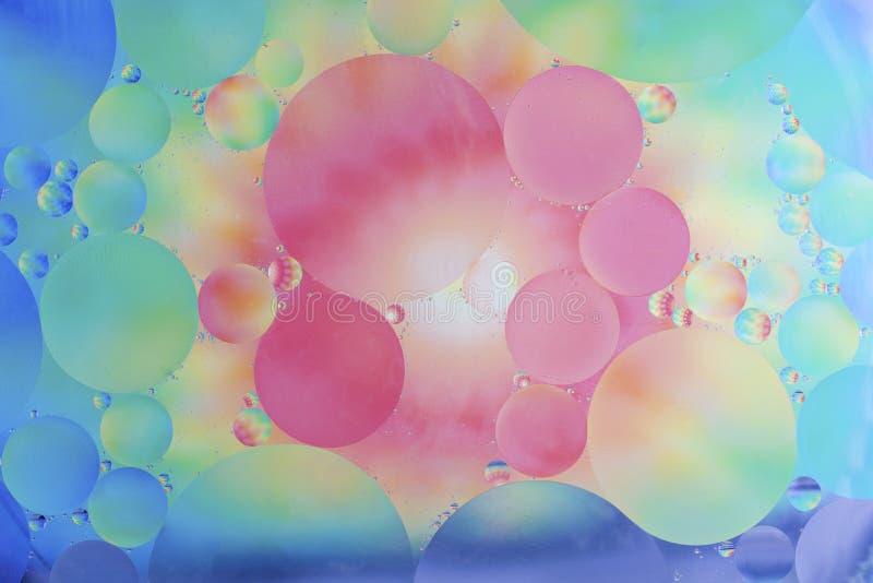 Lubrifique gotas no macro da água com um fundo colorido foto de stock