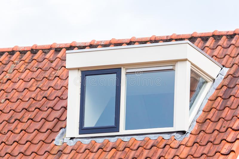 Lucarne sur le toit du grenier avec des tuiles de toit images stock