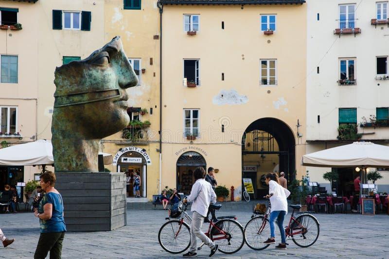 LUCCA, ITALIA - 5 DE OCTUBRE DE 2017: Los pares con las bicicletas caminan el cuadrado cuadrado famoso del anfiteatro (plaza Anfi fotografía de archivo libre de regalías