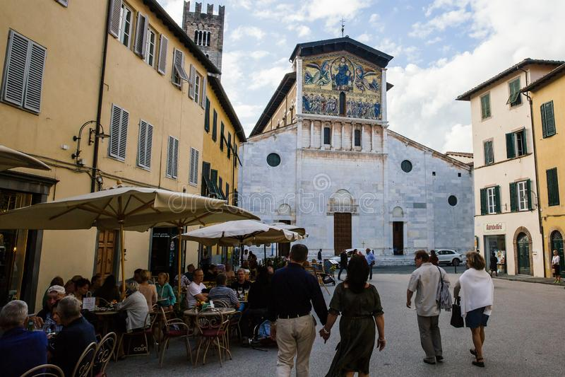 LUCCA, ITALY - OCTOBER 5, 2017: People walk in the square in front of San Frediano Basilica. Typical lifestyle scene of ancient. Touristic italian place royalty free stock photo