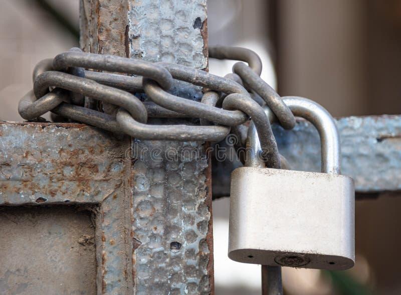 Lucchetto di metalli pesanti con il primo piano a catena su un portone dell'entrata fotografia stock libera da diritti