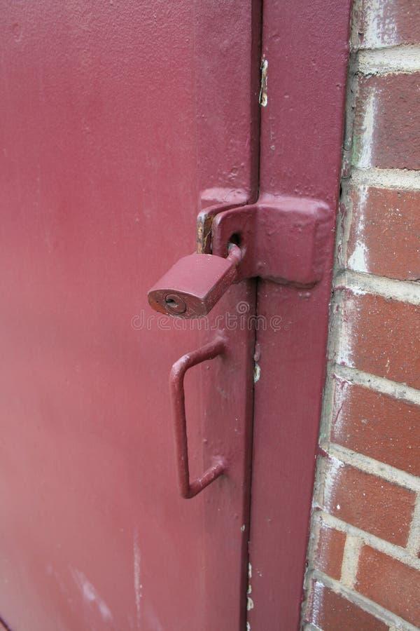 Lucchetto dipinto rosso sulla porta bloccata fotografie stock
