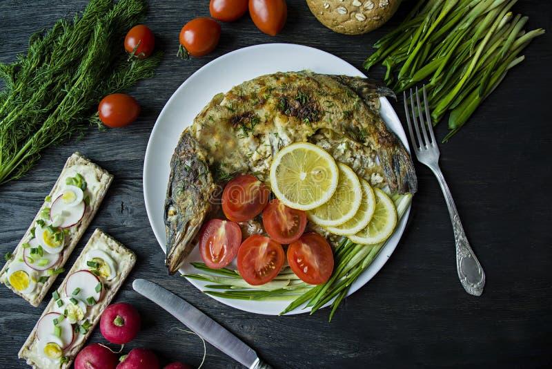 Luccio cotto nel forno, decorato con le verdure e le erbe Servendo su un piatto Nutrizione adeguata Priorit? bassa di legno scura fotografie stock