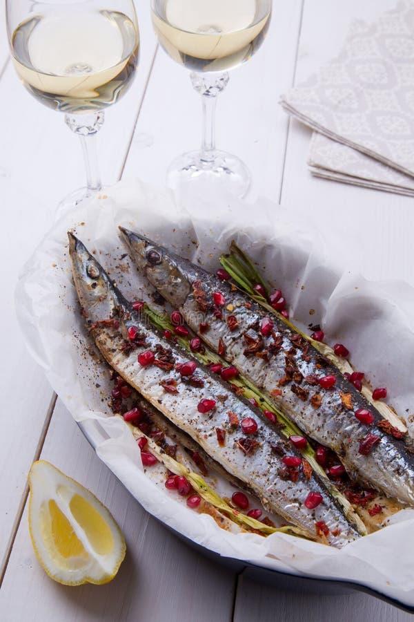 Luccio sauro con la miscela dei peperoni, della cipolla verde e dei semi del melograno con due vetri di vino bianco immagine stock
