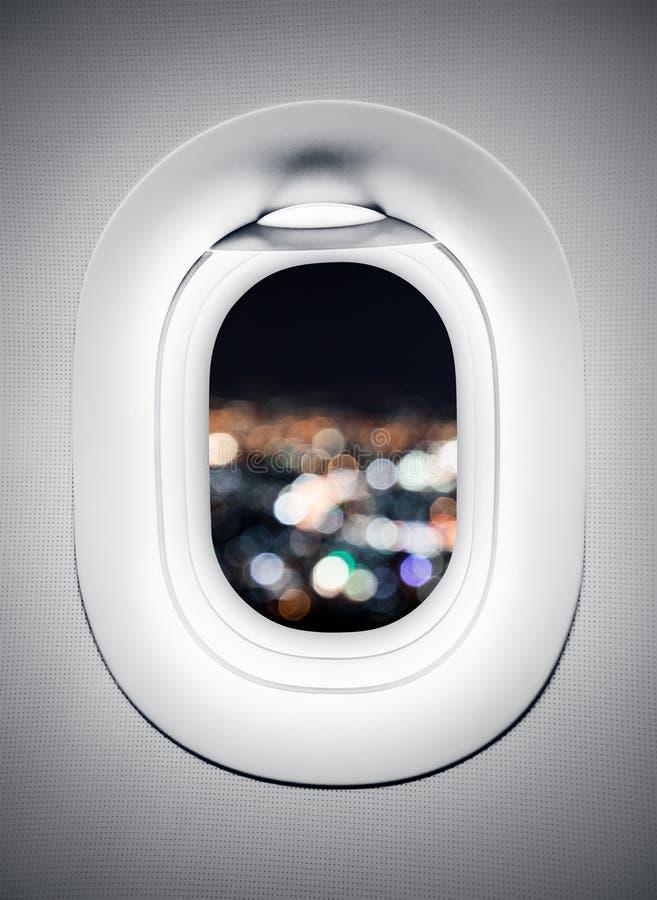 Luce della città della sfuocatura alla finestra dell'aeroplano fotografia stock