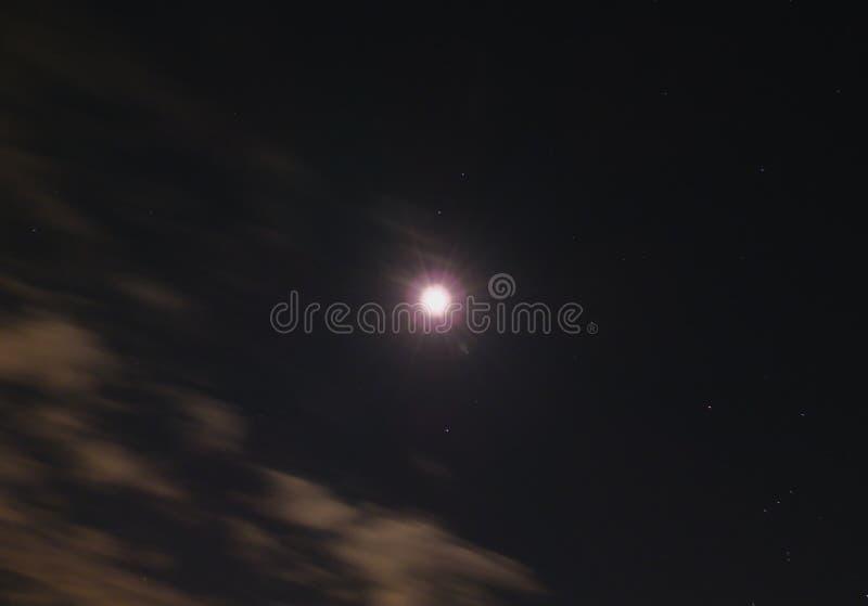 Luce della luna che irradia giù al cielo stellato della macchina fotografica poche nuvole fotografia stock libera da diritti