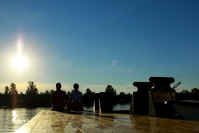 Luce della parte posteriore di profilo di tramonto delle coppie in lago fotografia stock libera da diritti