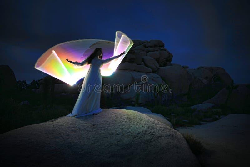 Luce della persona dipinta nel deserto sotto il cielo notturno immagine stock