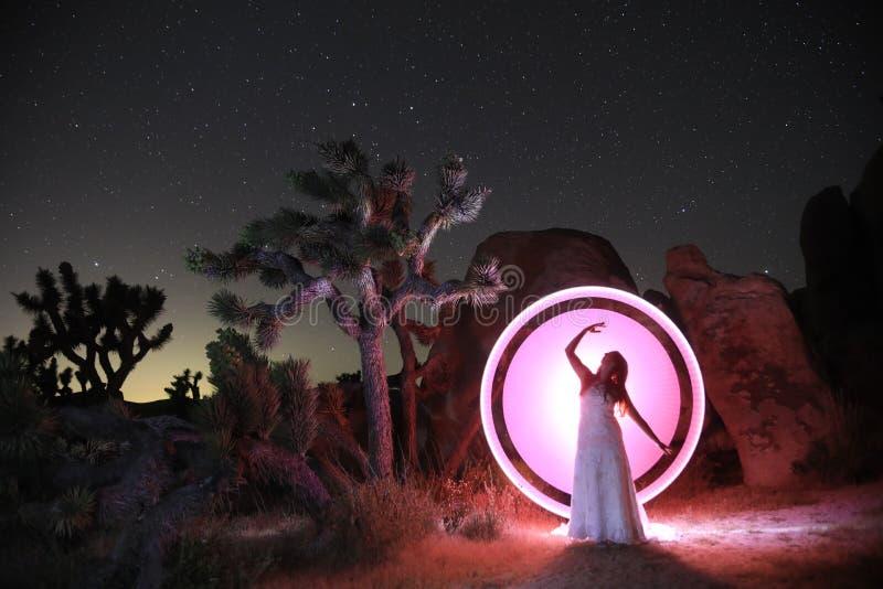Luce della persona dipinta nel deserto sotto il cielo notturno fotografia stock