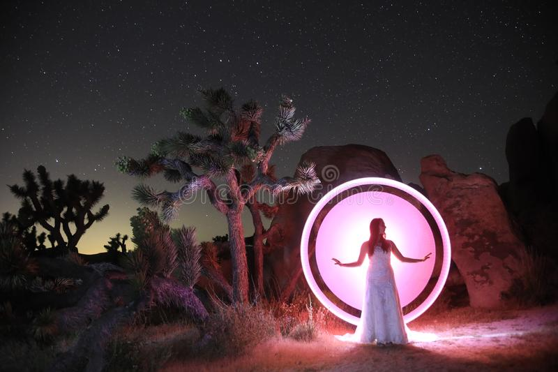 Luce della persona dipinta nel deserto sotto il cielo notturno fotografie stock