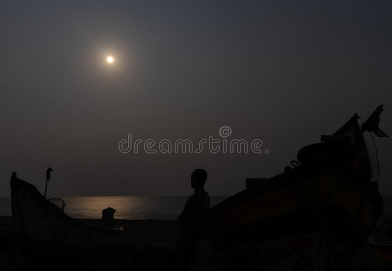 Luce di luna alla spiaggia con il pescatore e la sua ombra della barca fotografia stock