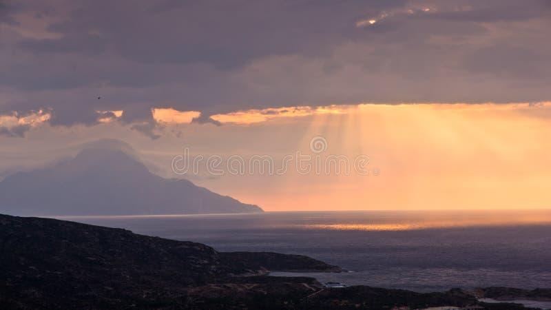 Luce divina, cielo tempestoso ed alba su un paesaggio intorno alla montagna Athos del san fotografia stock libera da diritti