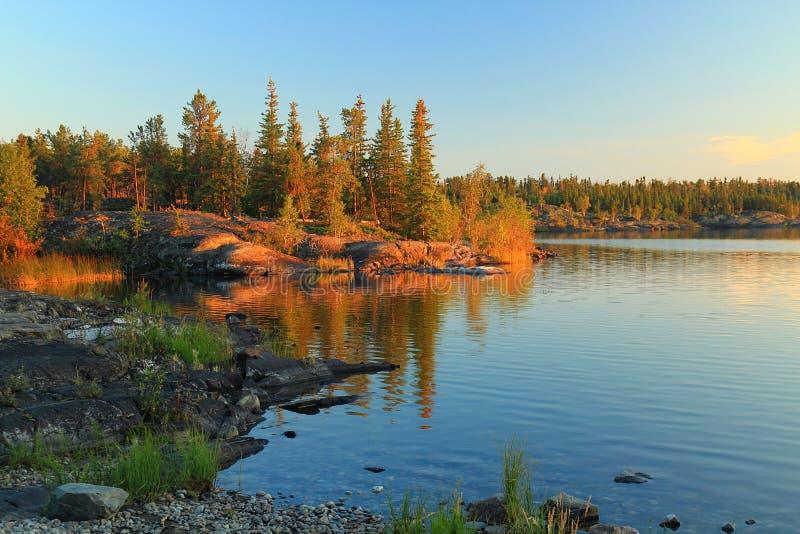 Luce dorata di sera nel lago frame vicino alla costruzione territoriale dell'Assemblea, Yellowknife, Territori del Nord Ovest fotografia stock libera da diritti