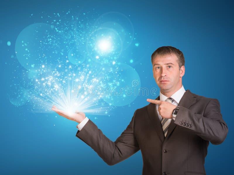 Luce magica della tenuta dell'uomo di affari a disposizione fotografia stock