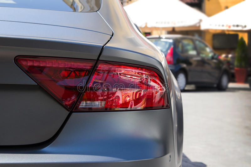 Luce posteriore dell'automobile grigia parcheggiata della grafite e del fondo blured fotografie stock