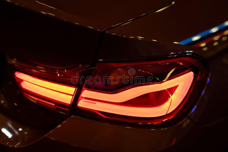 Luce posteriore rossa su un'automobile moderna con la riflessione Del primo piano l'automobile rossa della luce della coda indiet fotografie stock libere da diritti