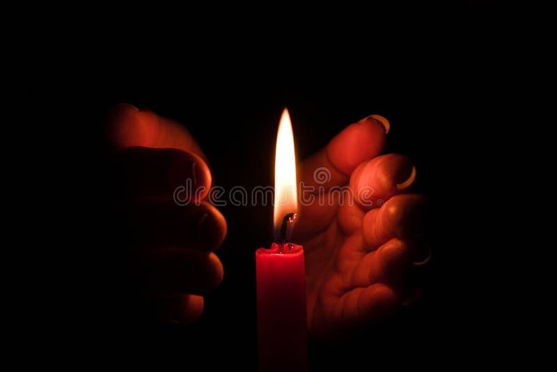 Luce proteggente della candela della mano dal vento fotografia stock libera da diritti