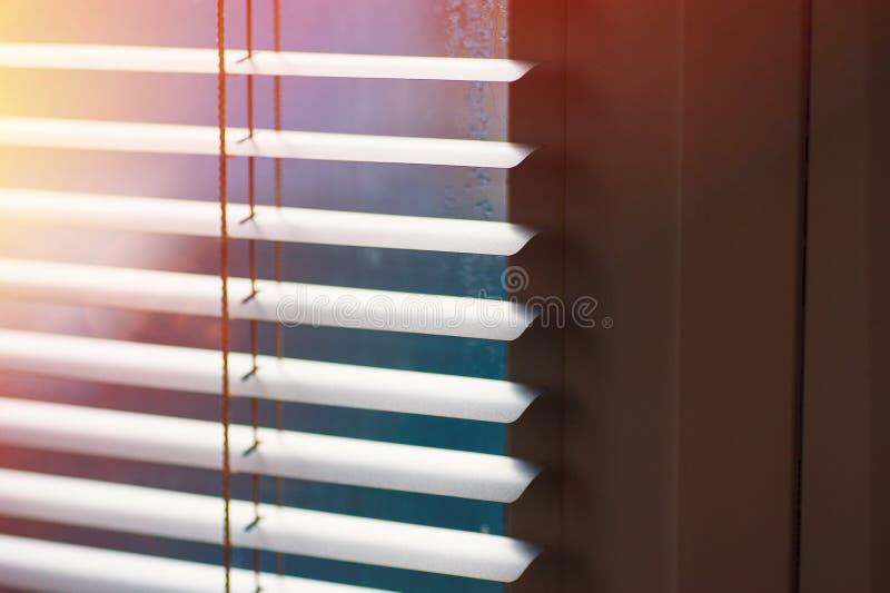 Luce solare che ottiene attraverso le veneziane la finestra fotografia stock
