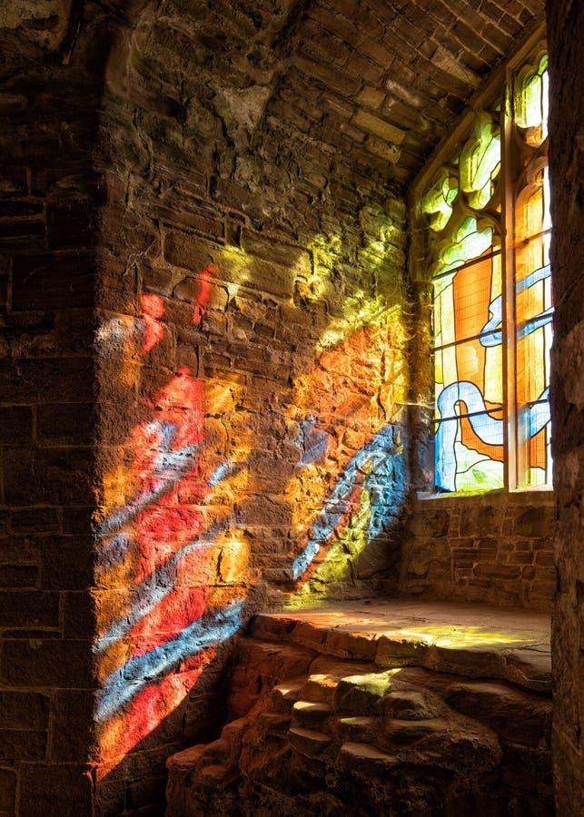 Luce solare che scorre attraverso una finestra di vetro macchiato, castello di Goodrich, Herefordshire fotografia stock libera da diritti