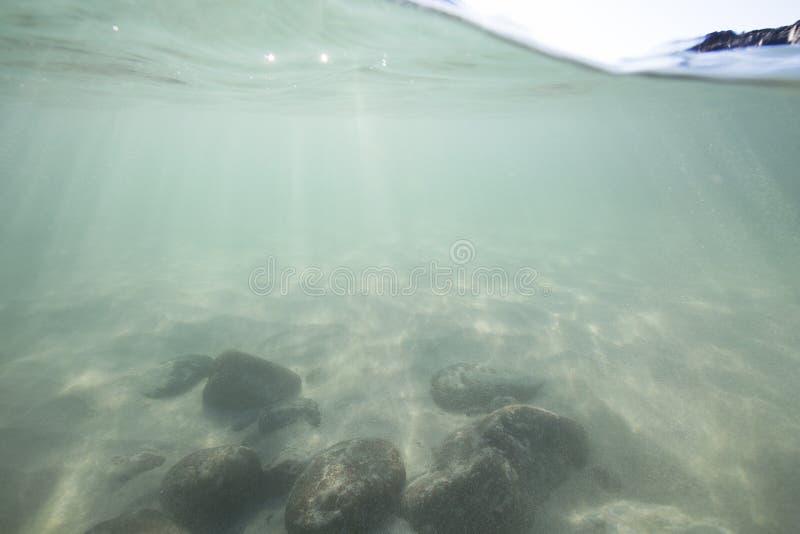 Luce solare che splende attraverso la superficie dell'oceano e che raggiunge il fondale marino, compreso la sabbia e le rocce bia fotografia stock libera da diritti