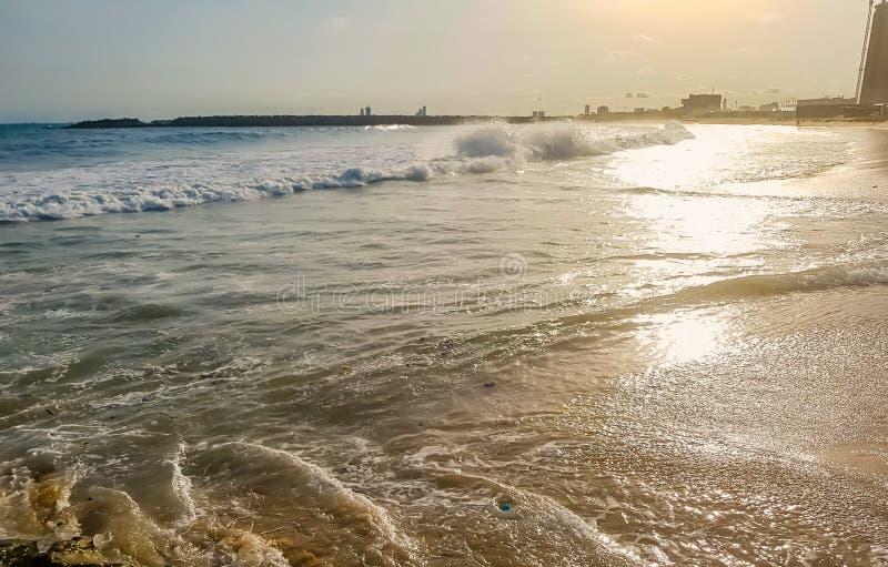 Luce solare dorata che riflette su una spiaggia a Lagos, Nigeria Esponga al sole splendere nella sera - onde che si rompono sulla fotografia stock libera da diritti