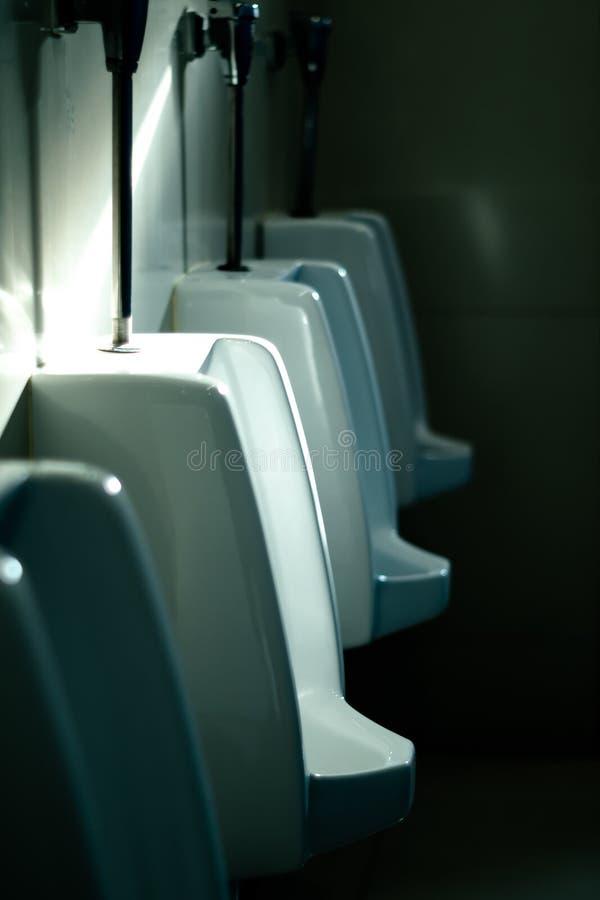 Luce solare sugli orinali bianchi nella toilette fotografia stock