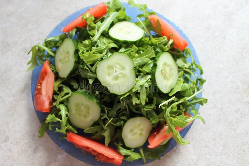 Luce verde ed insalata saporita con la rucola, il cetriolo ed il pomodoro fotografie stock libere da diritti