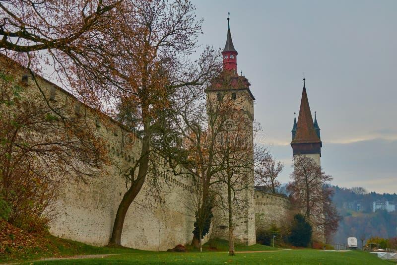 LUCERNA, SU??A - 29 de novembro de 2018: Ideia da parede velha de Musegg da parede da cidade e do outono atrasado das torres imagens de stock
