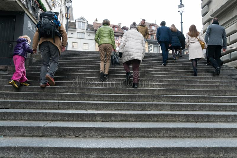 Lucerne, LU / Switzerland - November 9, 2018: many people of different age and gender rushing up and down old stone stairs in the royalty free stock images