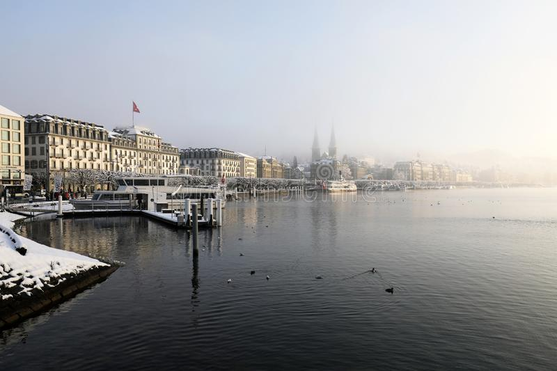 Lucerne, Switzerland, February 4, 2019: Lake Lucerne with pier and church of St. Leodegar on a mystical winter morning. In Lucerne stock photo