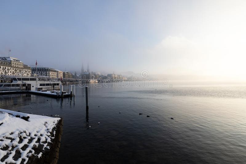 Lucerne, Switzerland, February 4, 2019: Lake Lucerne with pier and church of St. Leodegar on a mystical winter morning. In Lucerne stock photography