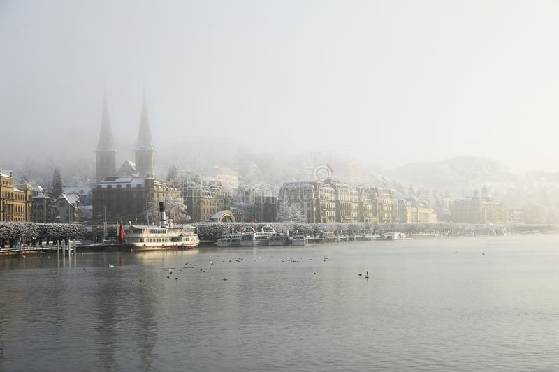 Lucerne, Switzerland, February 4, 2019: Lake Lucerne with pier and church of St. Leodegar on a mystical winter morning. In Lucerne royalty free stock images