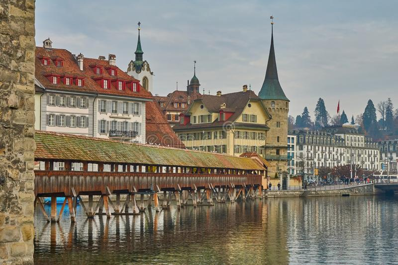 LUCERNE, SWITZERLAND - November 29, 2018: View of the Wooden Chapel Bridge, houses, old towers and spiers on the embankment stock photo