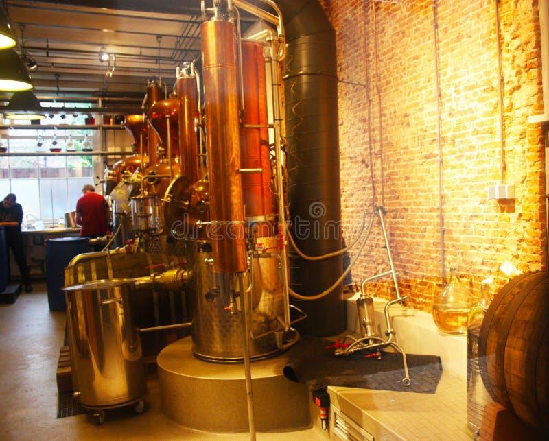 Luces anaranjadas en un cuarto interior de una destilería materiales del trabajo para producir los licores industria y maquinaria imagen de archivo