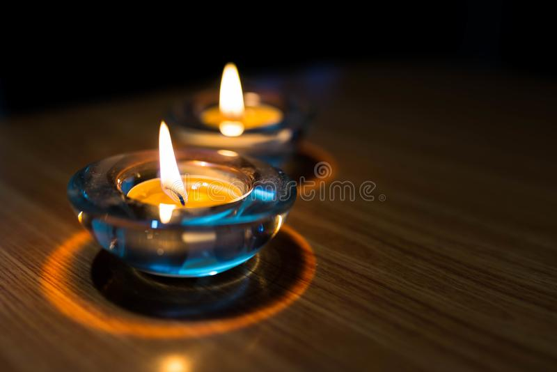 Luces ardiendo de la vela en la tabla de madera en un cuarto oscuro fotografía de archivo