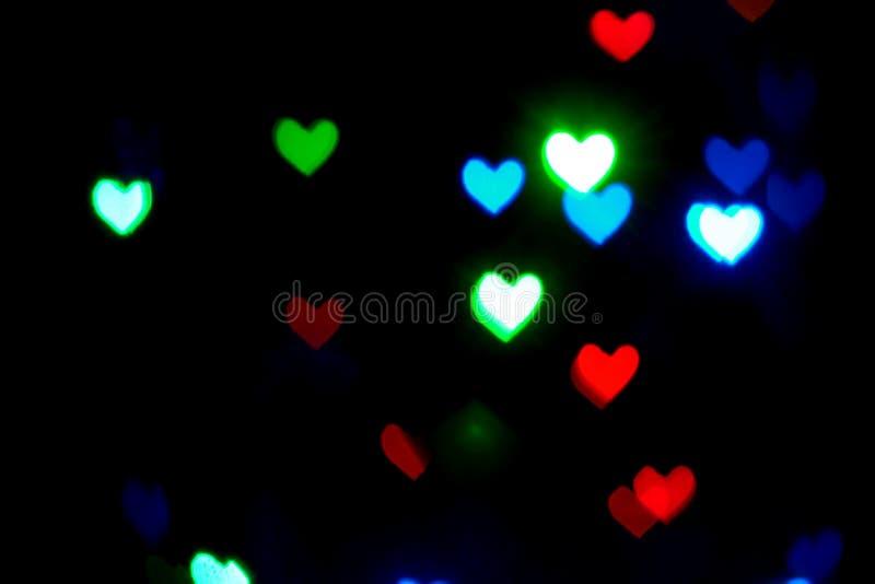 Luces borrosas coloreadas multi en la forma de corazones en la oscuridad imagenes de archivo