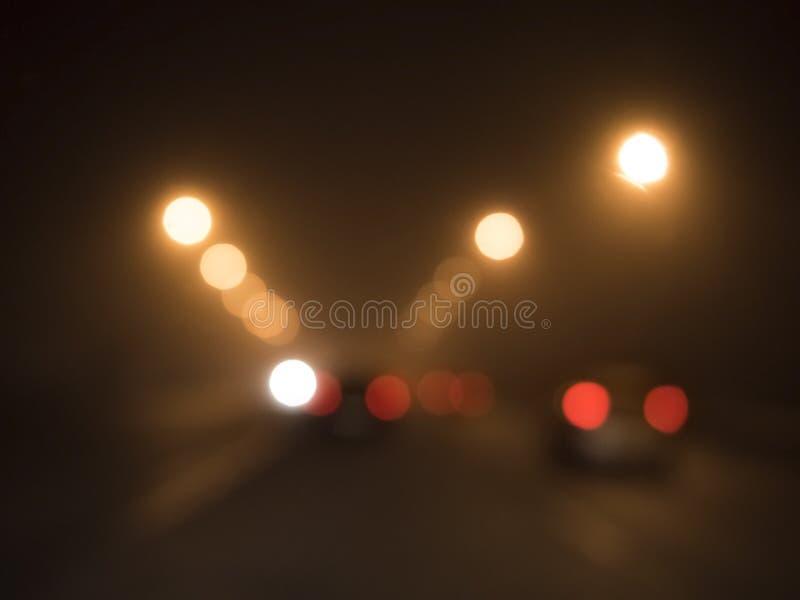 Luces borrosas de coches en el camino en la niebla imágenes de archivo libres de regalías