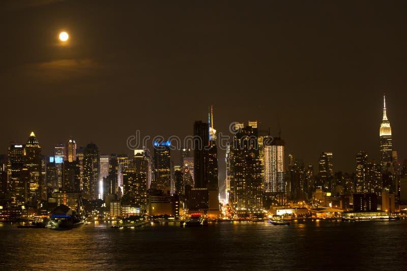 Luces calientes de la ciudad en una noche caliente debajo de una Luna Llena fotos de archivo libres de regalías