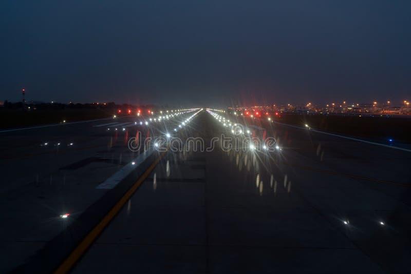 Luces de aterrizaje EN una pista del aeropuerto en el cielo nocturno imagen de archivo libre de regalías