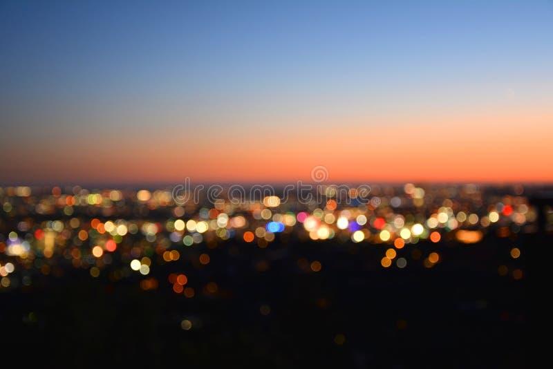 Luces de Bokeh de una ciudad en la puesta del sol fotografía de archivo libre de regalías