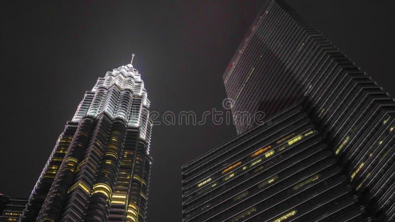 Luces de la ciudad de la noche Hermosa vista de emerger imponente de la torre de Petronas majestuoso sobre distrito de KLCC fotografía de archivo